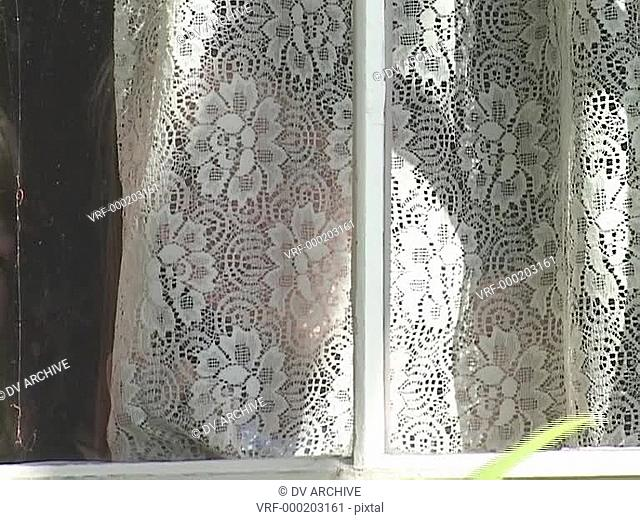 A girl looks through lace window curtains