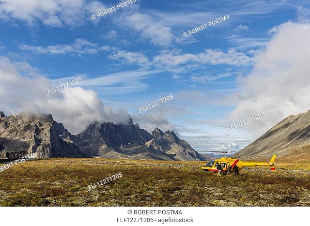 Three men get out of a helicopter on a mountain top in Tombstone Territorial Park; Yukon, Canada