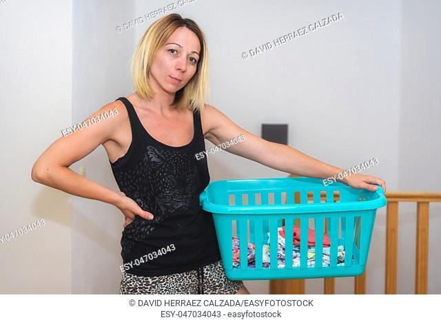 Young woman doing housework holding a basket with laundry