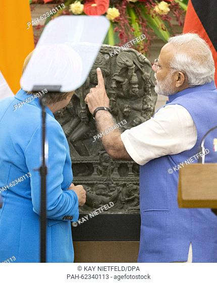 German chancellor Angela Merkel symbolicly hands over the statue of Hindu goddess Durga to Indian Prime Minister Narendra Modi at the Hyderabad House after the...