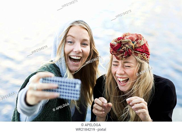 Cheerful female college students taking selfie through mobile phone against river