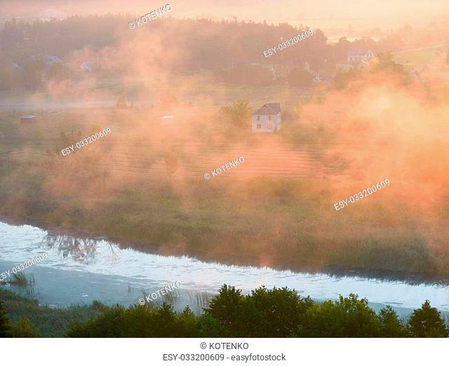 Summer landscape with a house in the fog. View from the hill. Morning mist over the river. Ukraine, Europe
