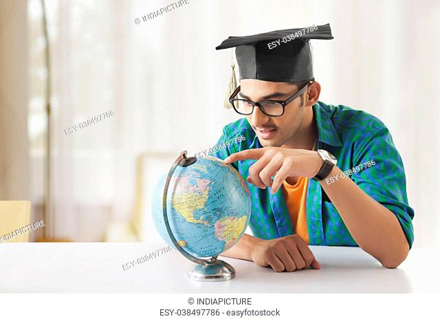 Young man leaning at desk with globes