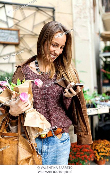 Smiling woman with flowers and cell phone outdoors