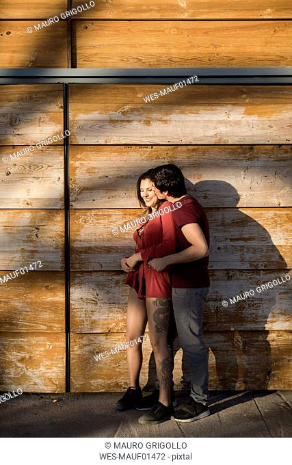 Happy affectionate young couple standing at wooden wall