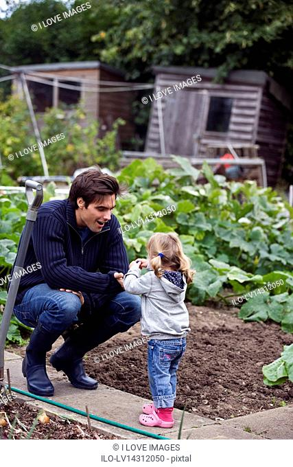 A father and daughter working on an allotment together