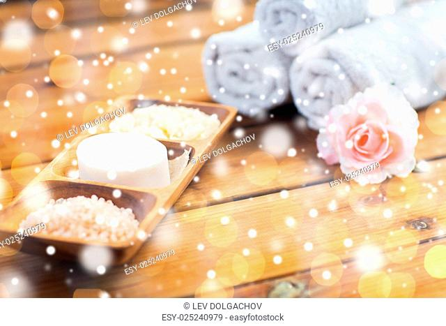 beauty, spa, bodycare, natural cosmetics and bath concept - soap with himalayan salt and scrub in wooden bowl on table over lights and snow