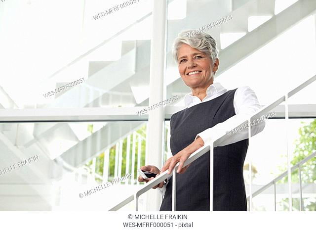 Smiling mature businesswoman on office staircase
