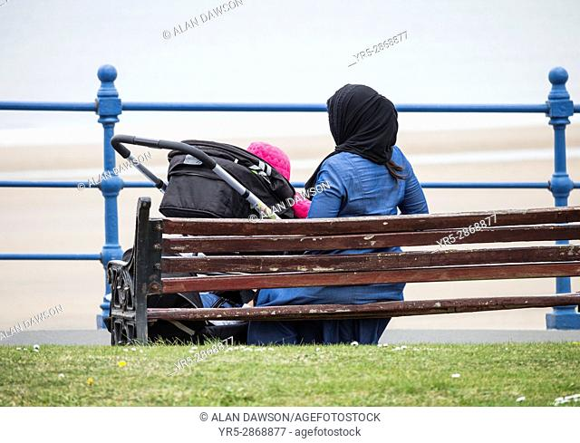 Seaton Carew, County Durham, north east England. United Kingdom. Woman wearing Hijab headwear sitting on seat overlooking the beach on a cold, overcast day