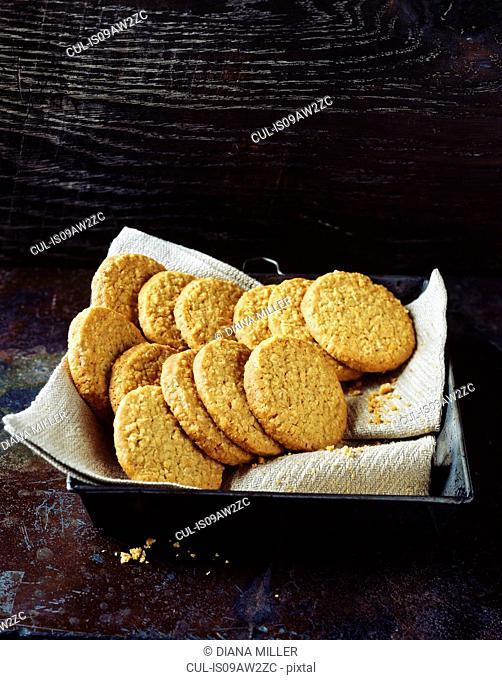 Homemade oatmeal cookies on tea towel in baking tray