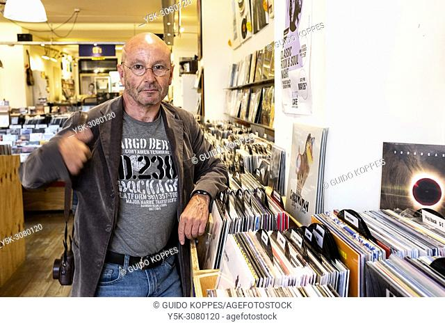 Tilburg, Netherlands. A Mature adult balding man visiting a vintage Vinyl record store to find his kind of music. Now sales of CD's are in decline
