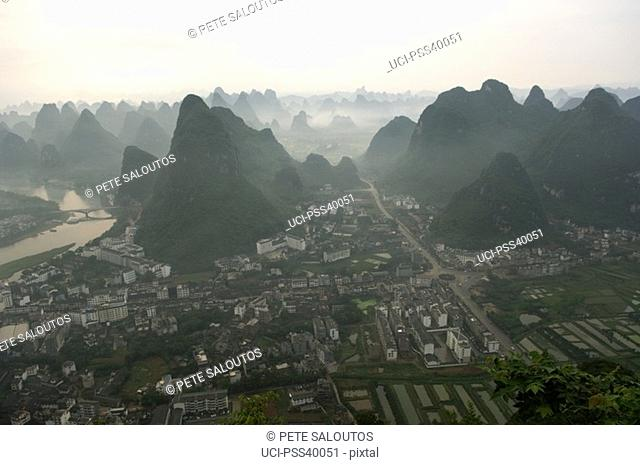 Aerial view of mountains and city in valley, Guilin, China