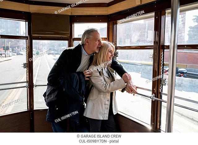 Senior couple riding on tram in city
