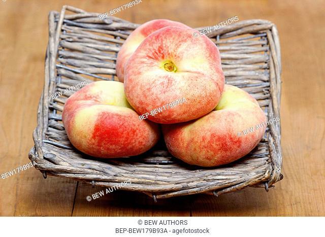 Donut peaches, saturn peaches in wicker basket