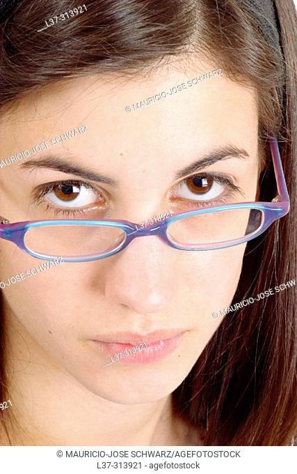 Young black-haired girl looking at the camera over her blue eyeglasses