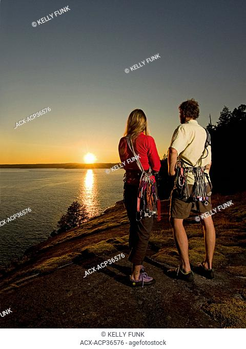 A young couple stops to check out the sunset after rock climbing at Stillwater bluffs near Powell river on the upper Sunshine coast