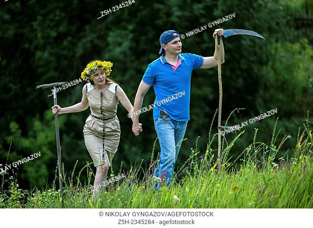 Young couple with an agricultural tool in the field