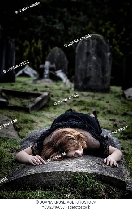 a woman is lying on a tomb