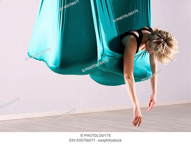 Single athletic woman leaning downward while doing intense leg and hip stretching exercises wrapped in aerial yoga blanket suspended from ceiling