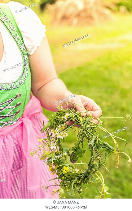 Germany, Saxony, woman wearing dirndl holding floral wreath, close-up