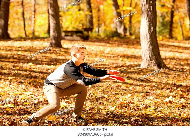 Teenage boy catching flying disc in autumn forest