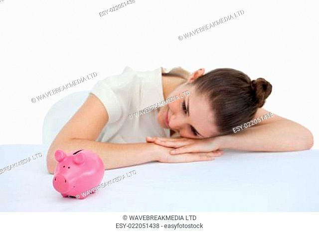 Young businesswoman leaning on her desk with a piggy bank