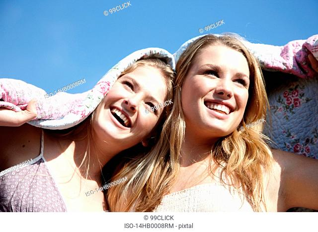 Two girls wrapped in a blanket outdoors