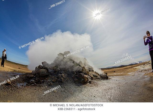 Photographer in geothermal field of mud pots, steam vents, and sulphur deposits at Hverarönd, Iceland