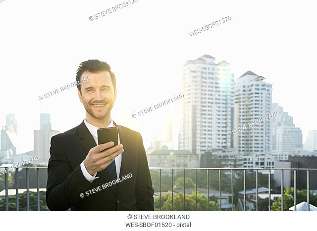 Business man in dark suit with smartphone on city rooftop