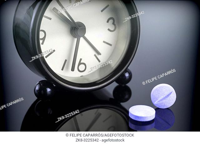 Blue pills next to a clock, conceptual image