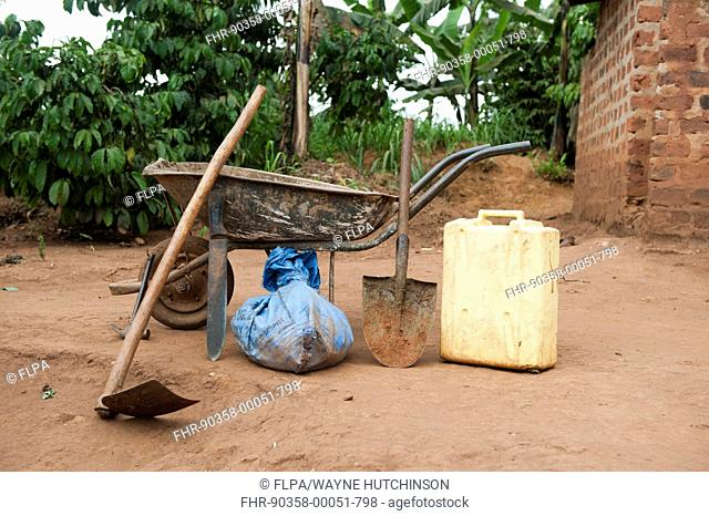 Basic tools for farming, hoe, machette, shovel, water container and wheelbarrow, Uganda, June