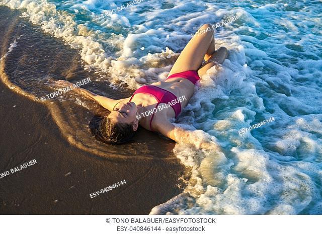 Bikini girl relaxed lying on the beach sand shore water of Mediterranean sea