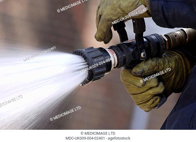 A fire fighter from the Hertfordshire Fire & Rescue Service, UK, grasping a hose nozzle of with water streaming from it. In December 2005