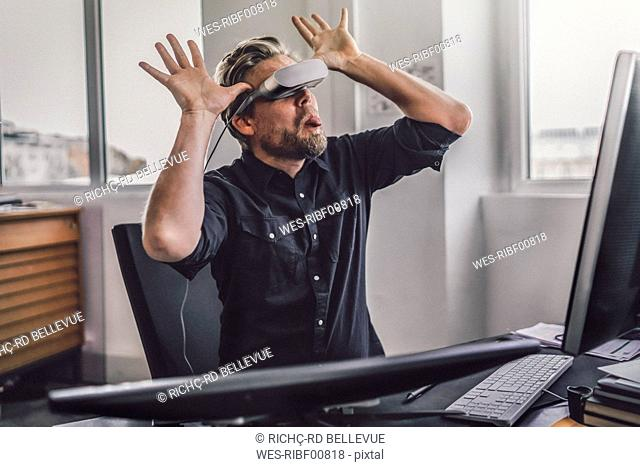 Graphic designer wearing VR glasses, sticking tongue out, mocking mischieviously