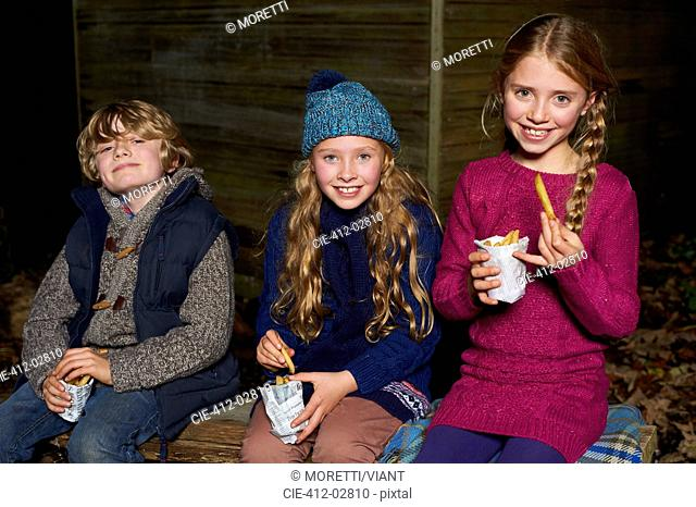 Smiling children eating french fries at night