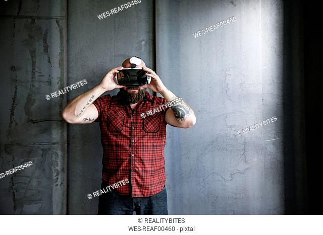 Bearded man wearing VR glasses