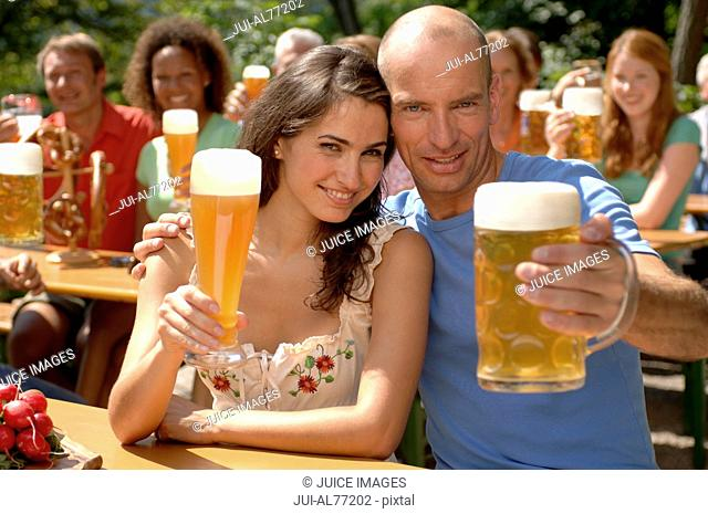 View of a crowd of people raising their drinks, beergarden, Munich, Bavaria, Germany