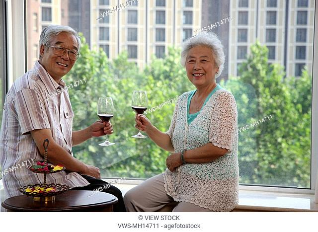 Mature couple drinking red wine at table