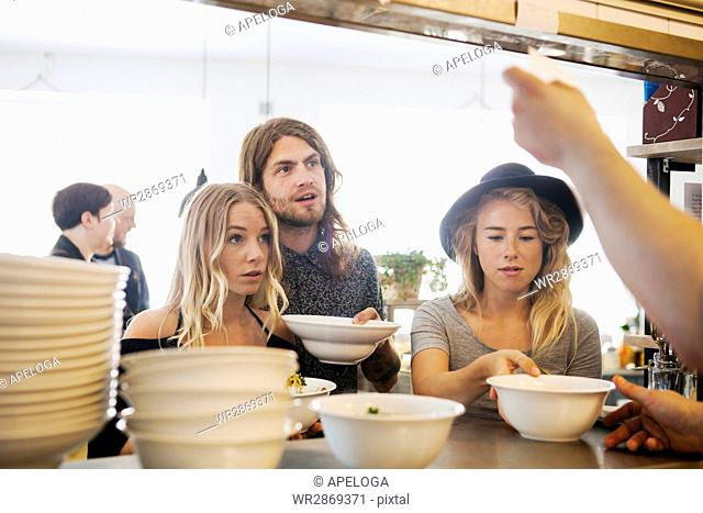 Male and female friends receiving order from chef at restaurant