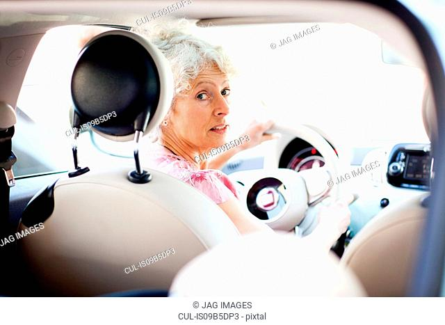 Portrait of mature woman looking over her shoulder in car