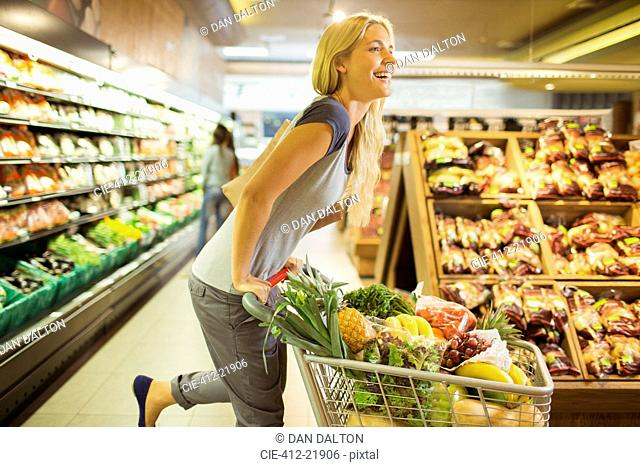 Woman playing with shopping cart in grocery store