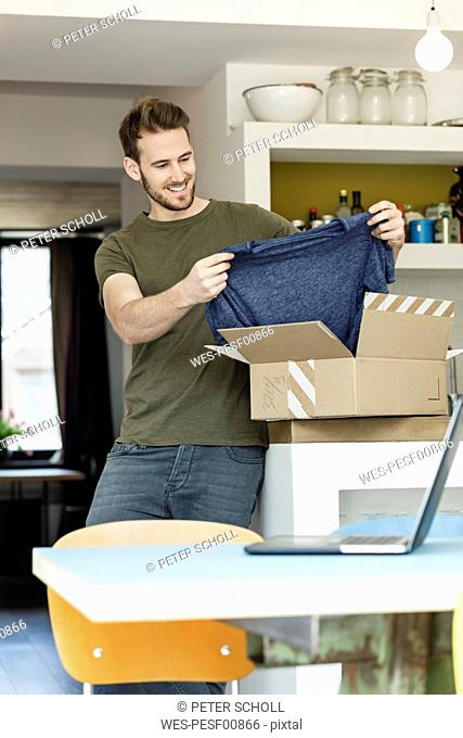 Smiling young man at home unpacking parcel with clothing