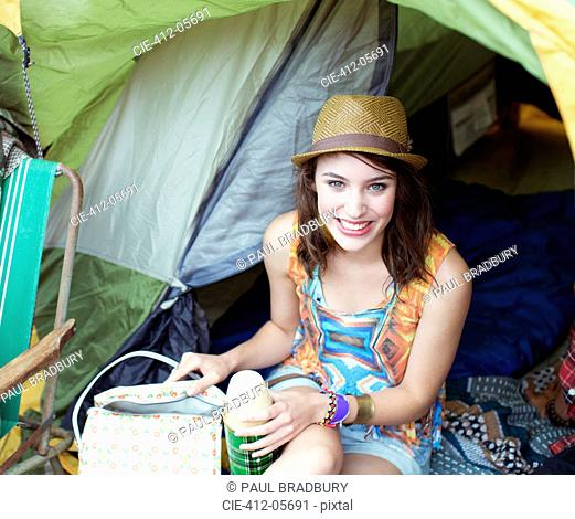 Portrait of smiling woman in tent at music festival