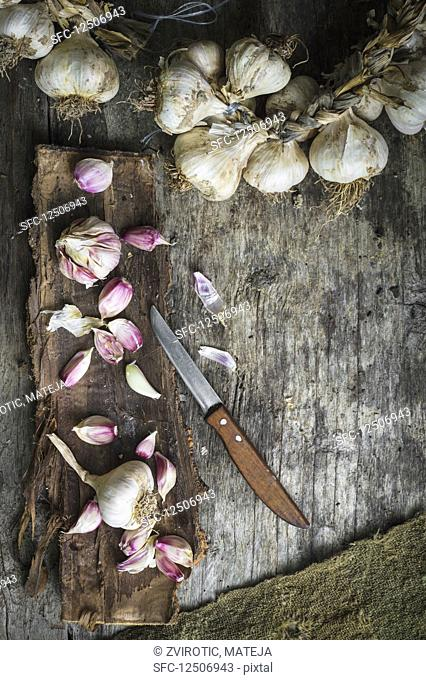 Opened garlic bulbs on tree bark and garlic wreath on rustic wooden surface