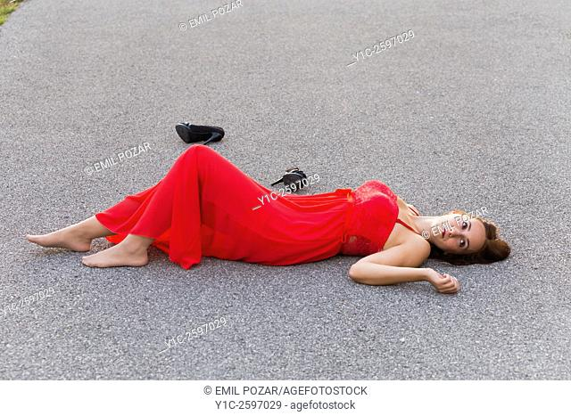 Lying on road in long Red dress young woman detached shoes