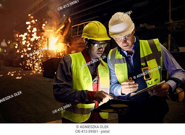 Steelworkers using digital tablets in steel mill