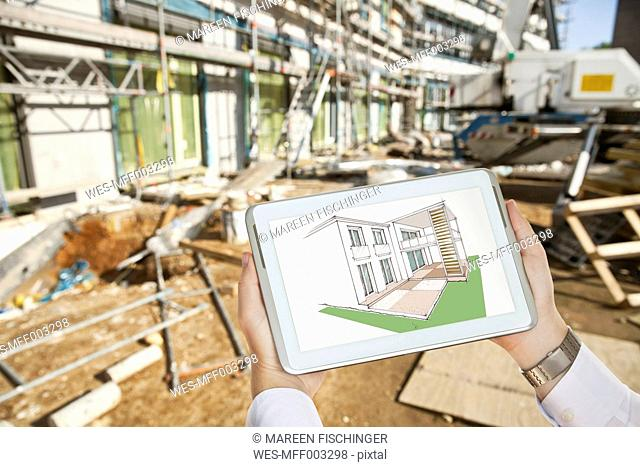 Hands holding a digital tablet with an architectural house sketch in front of a contruction site