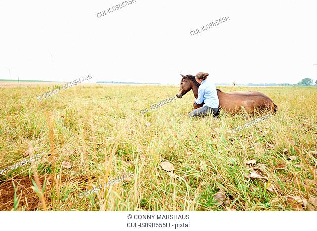 Woman crouching with arm around horse lying down in field