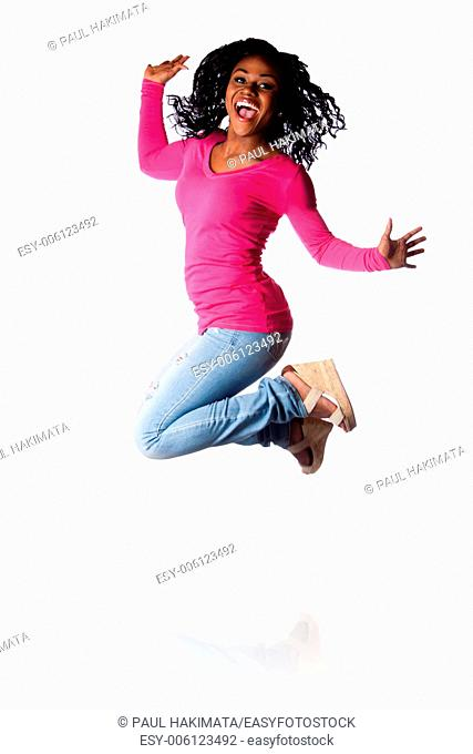 Beautiful young woman jumping of happiness celebrating and cheering, wearing blue jeans and pink shirt