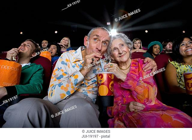 Senior couple sharing drink in cinema, low angle view